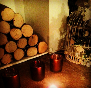 Wooden logs, candles and a birdcage creating hygge in the home