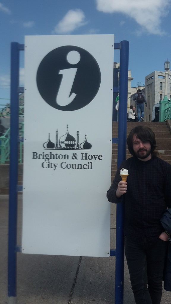 Dan eating ice cream standing next to Brighton & Hove City Council sign
