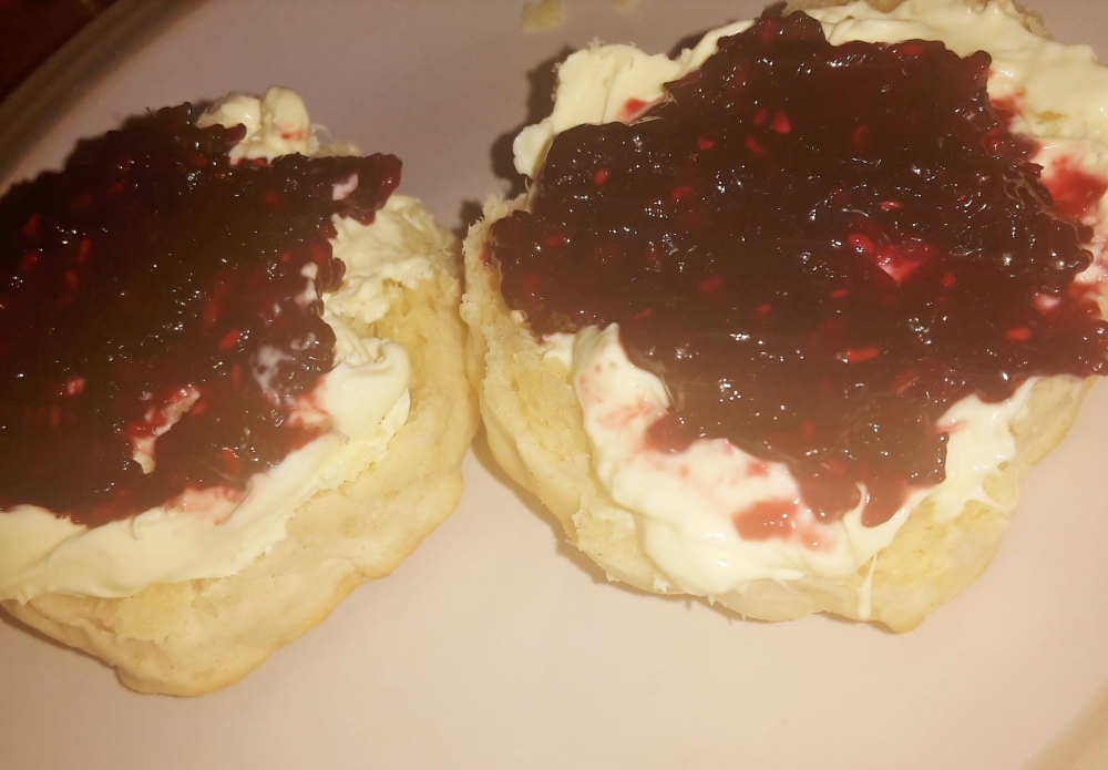 Scones topped with clotted cream and homemade blackberry and raspberry jam