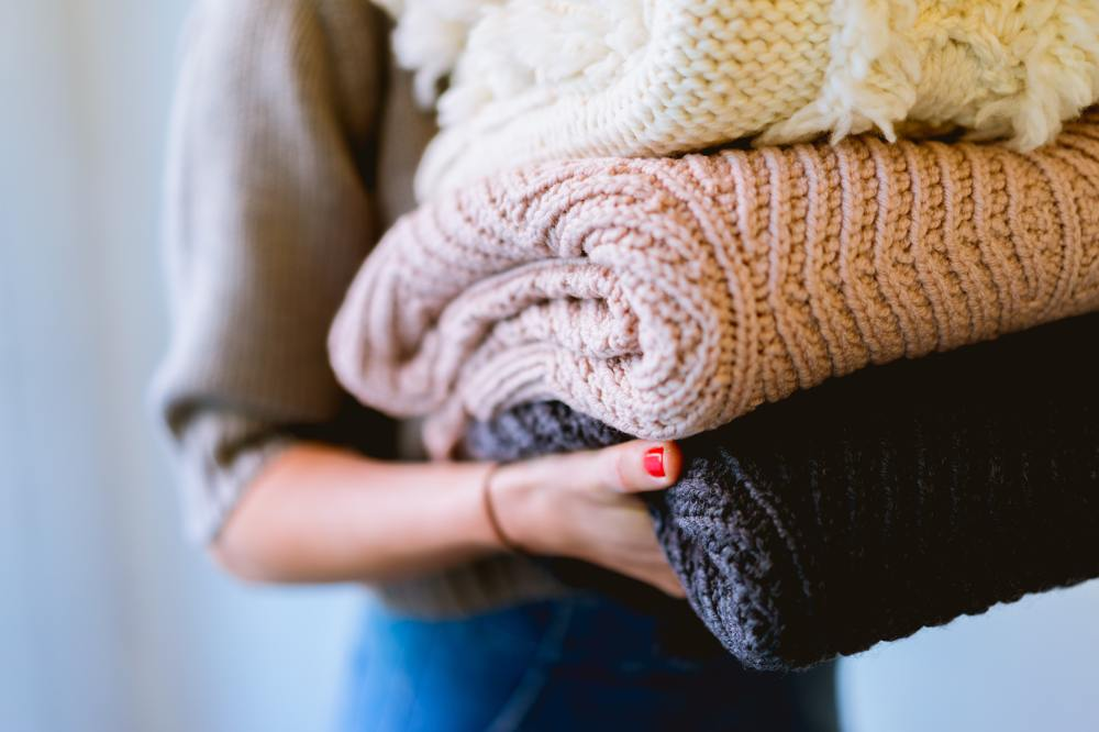 Woman carrying three woolly blankets